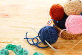 Balls of yarn and knitting needles on board — Photo