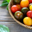 Small colored tomatoes in a basket — Stock Photo #50684535