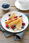 Delicious pancakes, crepes with raspberries and blueberries — Stock Photo