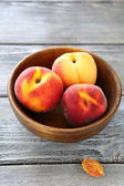 Fragrant and fresh peaches in wooden bowl — Foto de Stock