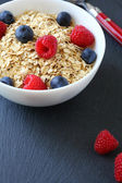 Flakes with berries in a bowl — Stock Photo