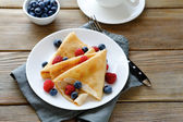 Summer crepes with berries on white plates — Stock Photo