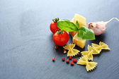 Pasta, cheese and tomatoes on slate background — Stock Photo