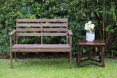 Wood bench decorated with white roses — Stock Photo