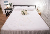 Honeymoon bed decorated with white rose — Stock Photo