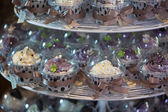 Colourful cupcakes on cakestand in a wedding party — Stock Photo