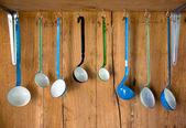 Variety of vintage enamel kitchen spoon with wooden background — Stockfoto