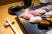 Fresh sushi on a black plate with chopsticks — Stock Photo