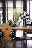 Wooden table and chair with a vintage polka dot lamp — Stock Photo