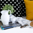 Jar, coffee cup and books with colorful pillows in background — Stock Photo