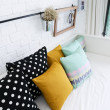 Colorful pillows on a sofa with white brick wall in background — Stock Photo #34921713