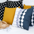 Colorful pillows on a sofa with white brick wall in background — Stock Photo #34921859