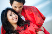 An in love young couple in romantic emotion with similar red dre — Stock Photo