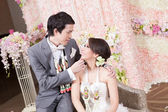 Newlywed bride and groom posing with Thai style garland and flow — Stock Photo