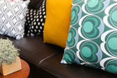 Close-up of colorful pillows on a leather sofa — Stock Photo