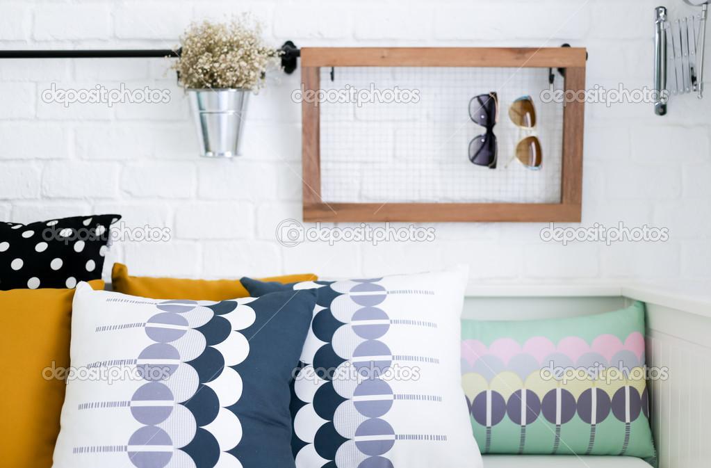 Cuscini colorati su un divano con mattoni bianchi a parete in sottofondo — Foto Stock © phaendin ...