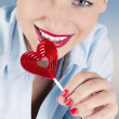 Woman with heart shaped lollipop — Stock Photo