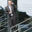 Businessman in front of the office building - Stock Photo