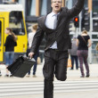 Businessman running through the streets — Stock Photo