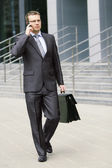 Businessman walking through the streets — Stock Photo