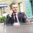 Businessman in sidewalk cafe — Stock Photo