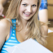 Beautiful female student in lecture hall — Stock Photo #18943007