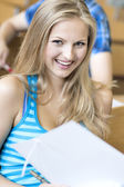 Beautiful female student in lecture hall — Stock Photo
