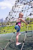 Girl climbing on rope ladder against sky — Stock Photo