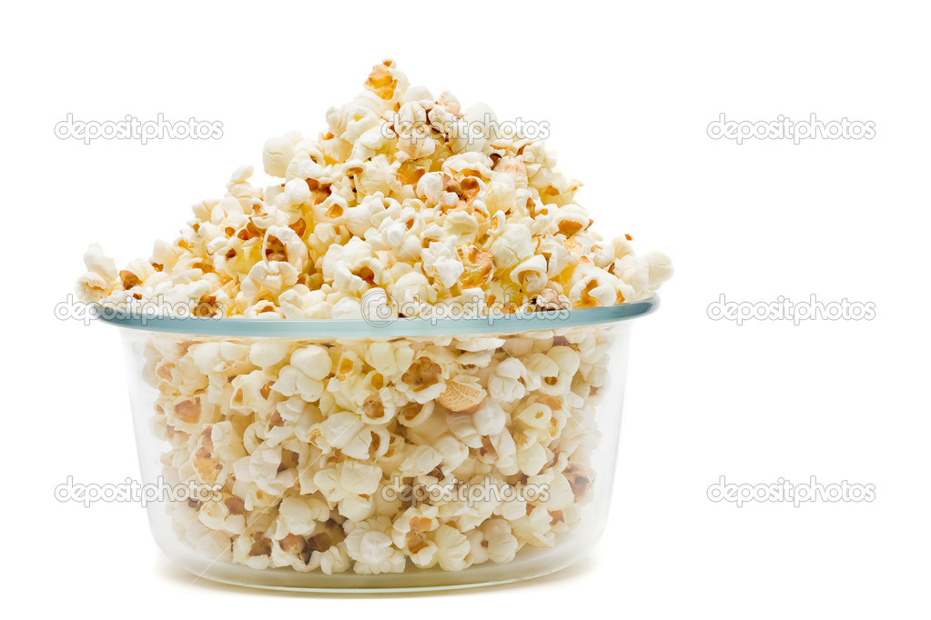 Delicious popcorn in glass bowl over white background — Stock Photo #18728919