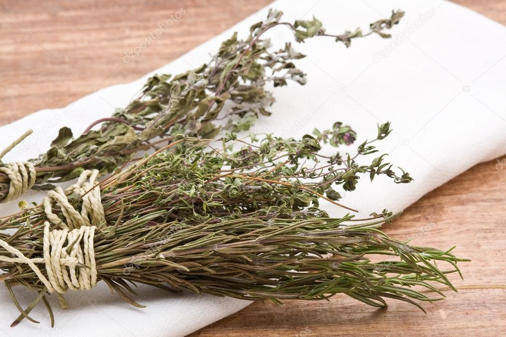 Fresh dried herb bundles of different herbs on wooden table — Stock Photo #18729991