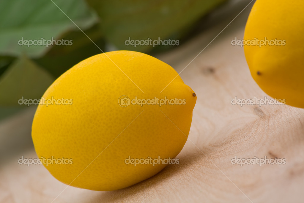 Fresh organic lemons with leaves on wood background — Stock Photo #18730023