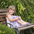 Little girl siting on the bench in the park — Stock Photo