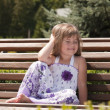 Little girl siting on the bench in the park — Stock Photo #18685425