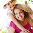 Stock Photo: Young mother giving piggyback to her daughter in the park