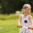Little girl ride the scooter in the park on green background — Stock Photo #18696315
