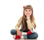 Cute little girl wearing jeans overall sitting on the floor and — Stock Photo