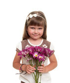 Cute little girl holding the bunch of flowers — Stock Photo