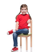 Little girl wearing red t-short and posing on chair — Stock Photo