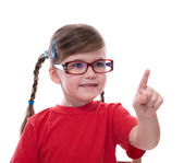 Little girl wearing glasses and pointing by forefinger to somewh — Stock Photo