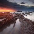 Dramatic sunrise over rocky shoreline with smoky sea — Stock Photo
