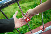 The bride and groom hold together their alliance lock — Stock Photo