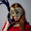 Beautiful young girl in a red dress and mask — Stock Photo