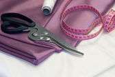 Large dressmaking scissors and pink measuring tape — Stock Photo