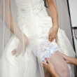 A bride is putting the garter on to stockings — Stock Photo