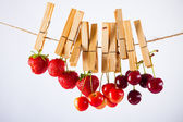 Cherry, strawberry and rope on white with clamp — Stock Photo