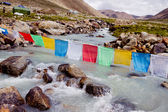 Mountain river and buddhist flags — Stock Photo