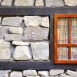 Wall of an old stone house with a window — Stock Photo