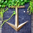 Decorative anchor on the mosaic wall with ivy growing on it — Stock Photo #36019899