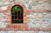 Wall of an old stone fence with a window — Stock Photo