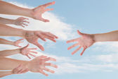 Hands reaching for a helping hand — Stock Photo